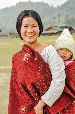 arunachal pradesh: Ziro, Arunachal Pradesh - circa March 2012: Pretty young woman in white t-shirt with red scarf carries her daughter on her back in Ziro, Arunachal Pradesh. Documentary editorial. Editorial