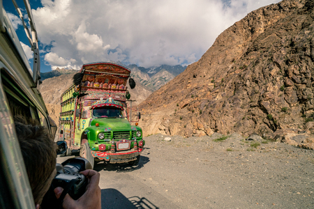 Traditional decorated truck in Pakistan on dangerous road in the mountains.