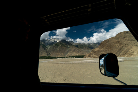 View of river Indus and Karakoram mountains from car window. Traveling in Pakistan. Foto de archivo - 118052189