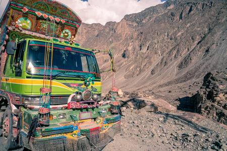 Decorated truck in Pakistan on dangerous road in the mountains.