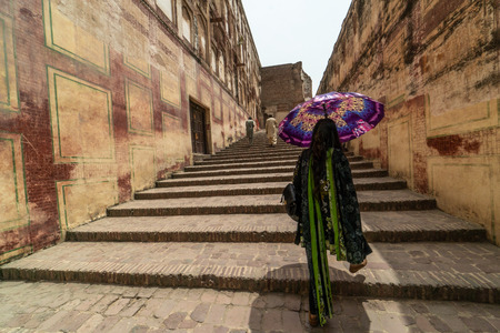 Historical staircase in old city of Lahore, Pakistan with local woman walking with her umbrella. Foto de archivo - 118052057