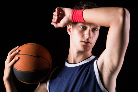 Basketball player wipes the sweat from his forehead Stock Photo