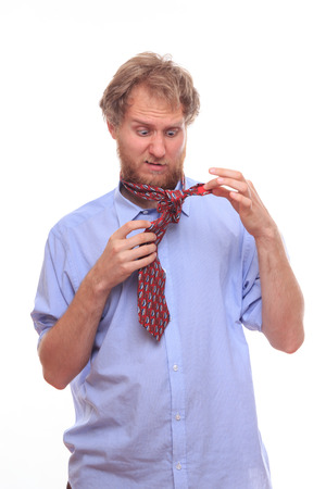 Man at morning trying to tie a tie on his neck photo