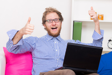 Man has joy at the computer on his knee