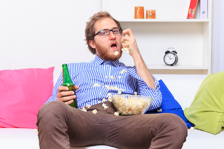 bad manners: Man eating popcorn on the sofa - studio shoot Stock Photo