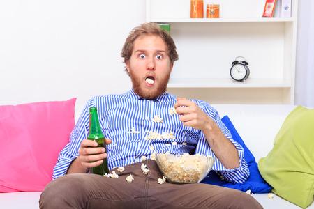 extrañar: Hombre sorprendido comiendo palomitas en el sofá en casa Foto de archivo
