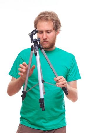 unfolding: Man unfolding a tripod - studio shoot Stock Photo