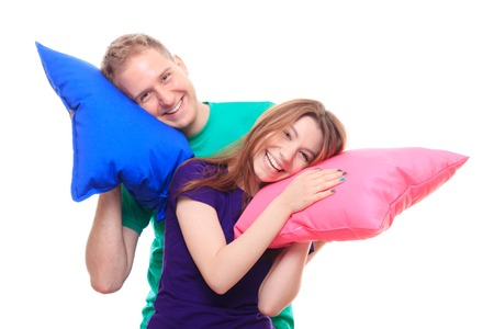 backgraound: Smiling man and woman holding colorful pillows - studio shoot
