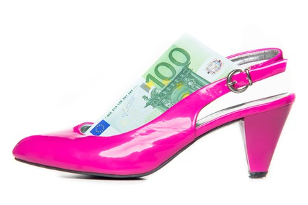 women's issues: Womens spending on shoes and clothes - ping heeled shoe and 100 euro - studio shoot Stock Photo
