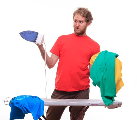 Embarrassed man irons clothes on board - studio shoot Stock Photo