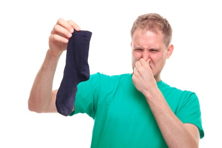 Man holding smelly socks and clogged nose - studio shoot Imagens
