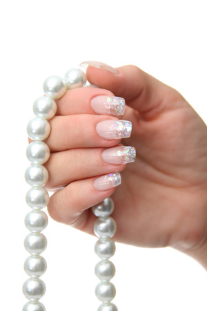 Woman hand holding pearl jewelery photo
