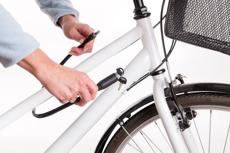 studio shoot: Securing the bike with a chain with a key - studio shoot Stock Photo