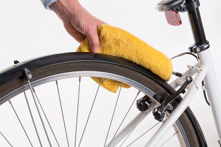 fender: Hands with a cloth and water cleaning bicycle fender - spring cleaning Stock Photo