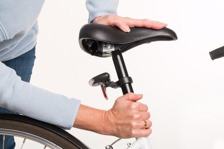 女性は - サイクリング前に自転車のサドルの高さを設定しますスタジオ撮影 写真素材