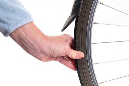 studio shoot: Hand checks the amount of air in a bicycle wheel - studio shoot