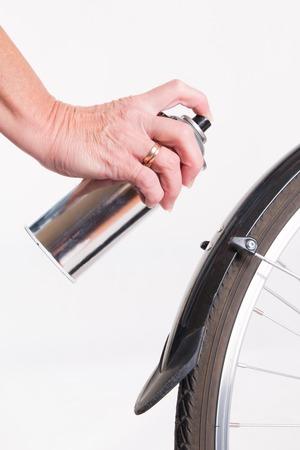 repaint: Woman paints the bike fender with spray - studio shoot