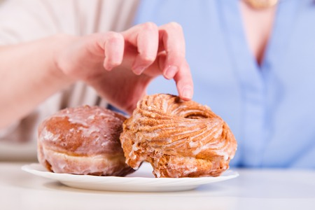 eating pastry: Hand reaches for the sweet donuts on the table in the kitchen Stock Photo