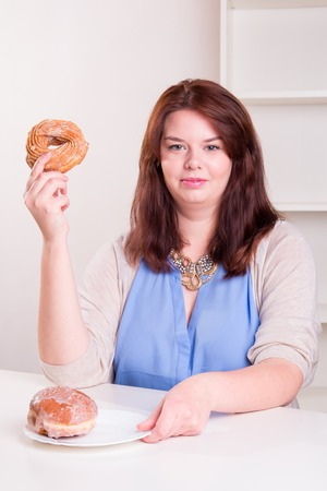 Plump woman holding a donut in her hand while sitting in the kitchen