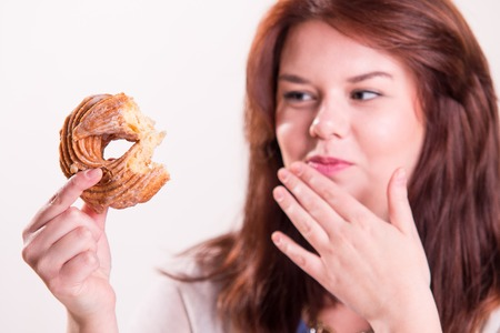 Plump and cheerful woman eating donuts at the table