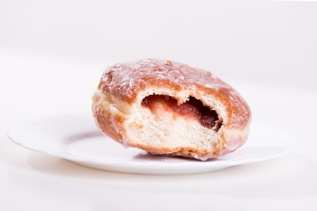 shrove: Bitten donut with jam lies on a plate - studio shoot Stock Photo