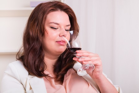 Plump and elegant woman tests a glass of red wine photo