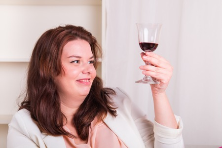 Plump and young woman tests a glass of red wine - studio shoot photo