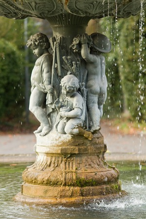 human source: Ornamental fountain with figures of children, park Stock Photo