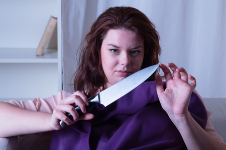 retaliation: Dangerous woman with a knife in his hand - studio shoot