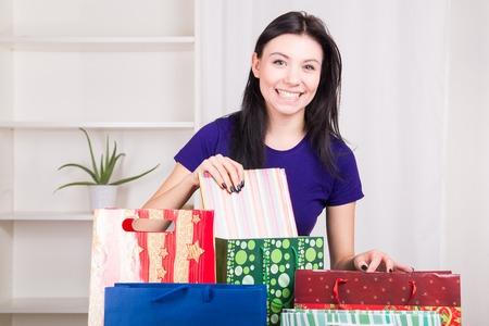 Smiling happy girl prepares bags gifts for Christmas - studio shoot photo