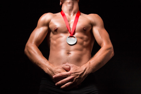 nacked: Bodybuilder with medal on his chest - studio shoot