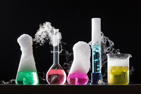 reaction: Glass in a chemical laboratory filled with colored liquid during the reaction - studio shoot