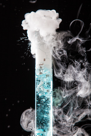 evaporate: Chemical reaction of blue liquid in raduated cylinder in labolatory - studio shoot