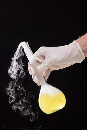 volumetric flask: Chemical reaction in volumetric flask glass kept in the hands of scientist - studio shoot