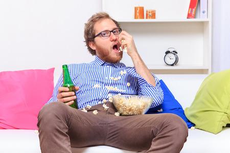 Uomo mangiare popcorn sul divano - riprese in studio
