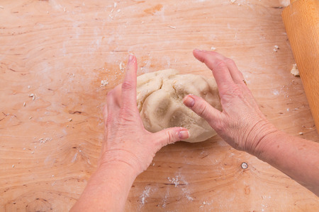 kneading: Hands kneading dough on board - flour and eggs