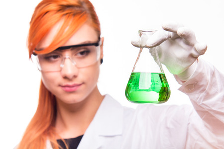 Chemist woman holding a test tube in a lab - studio shoot