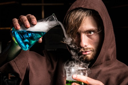 Alchemist in chemical laboratory prepares magical solution