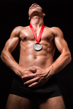 nacked: Muscular sportsmen with medal on his chest