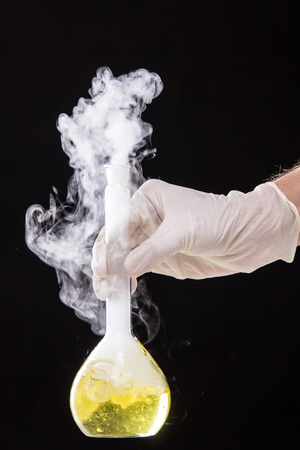 Chemical reaction in volumetric flask glass kept in the hands of scientist - studio shoot