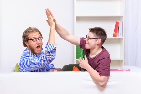 high: Giving friend a high five at home