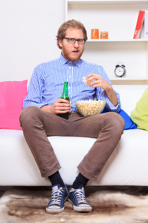 20 23 years: Surprised man on the sofa with popcorn