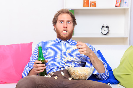 couch: Surprised man eating popcorn on the sofa