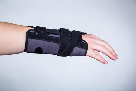 Hand in orthopedic orthosis on white backgroud