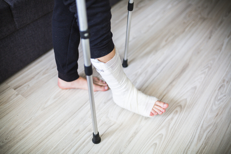 walking on crutches with a leg in a cast
