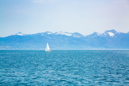 Lonely sailing boat on Lake Geneva and mountains in the background Stock Photo
