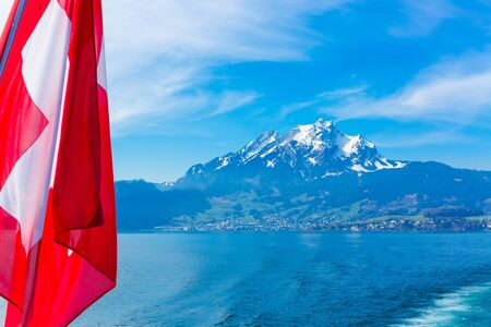 View of Pilatus Mountain and swiss flag from Lake Lucerne, Switzerland