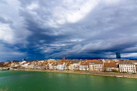 Basel architecture along Rhine River and storm clouds on the sky in Basel, Switzerland.