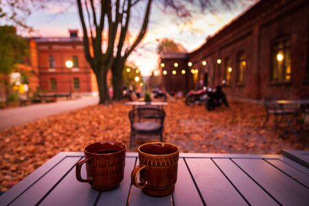 Lodz, Poland: A cup of hot drink on the table in the Ksiezy Mlyn historic distric during autumn evening