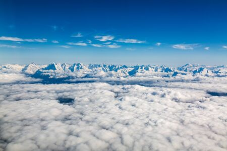 Aerial view of Alps mountain range above clouds seen from airplane over Switzerland Banco de Imagens